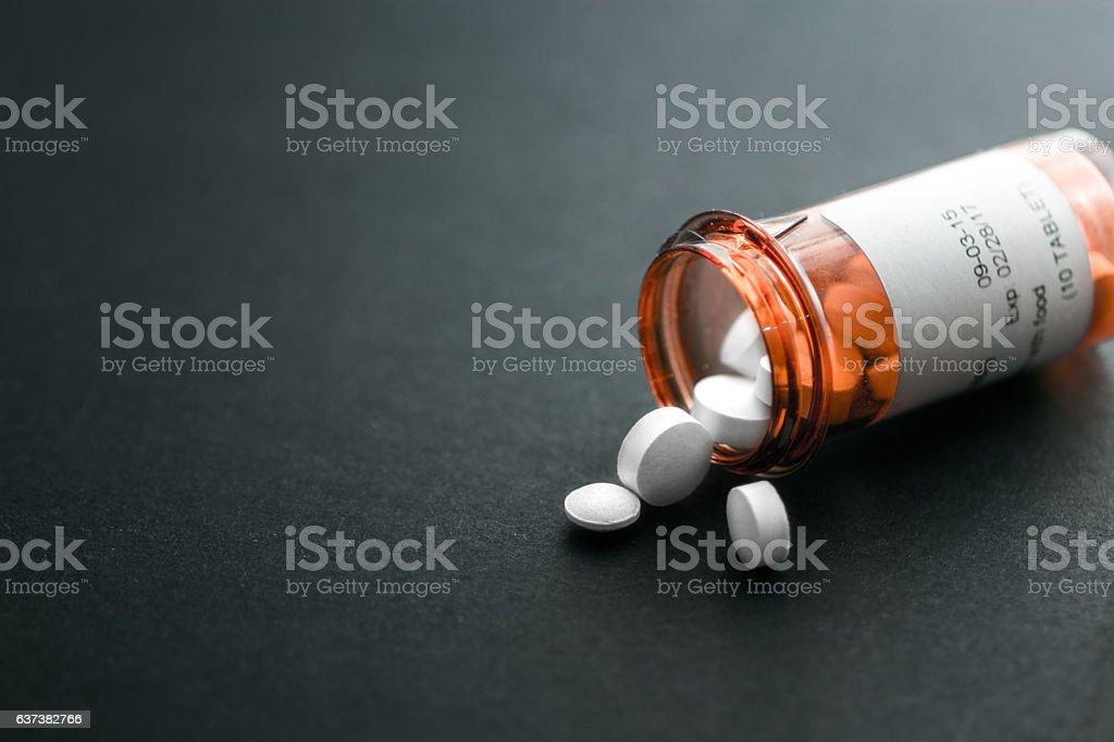 Pill bottle spilling out pills stock photo