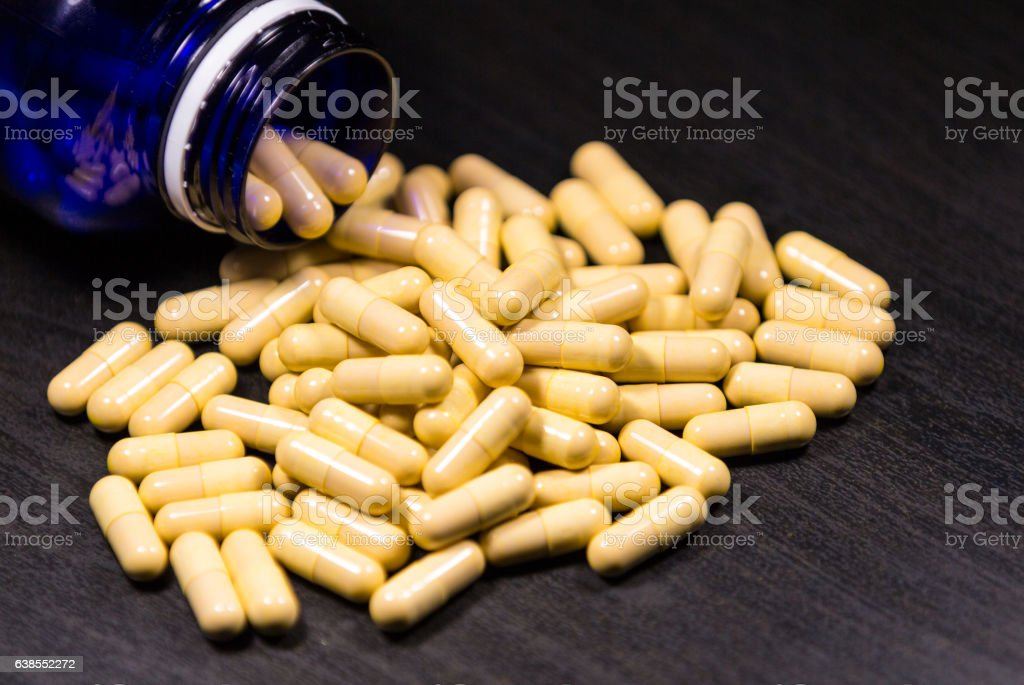 Pill bottle spilling pills on to surface stock photo