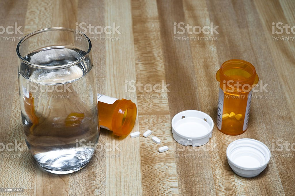 Pill Bottles and a Glass of Water on Counter stock photo