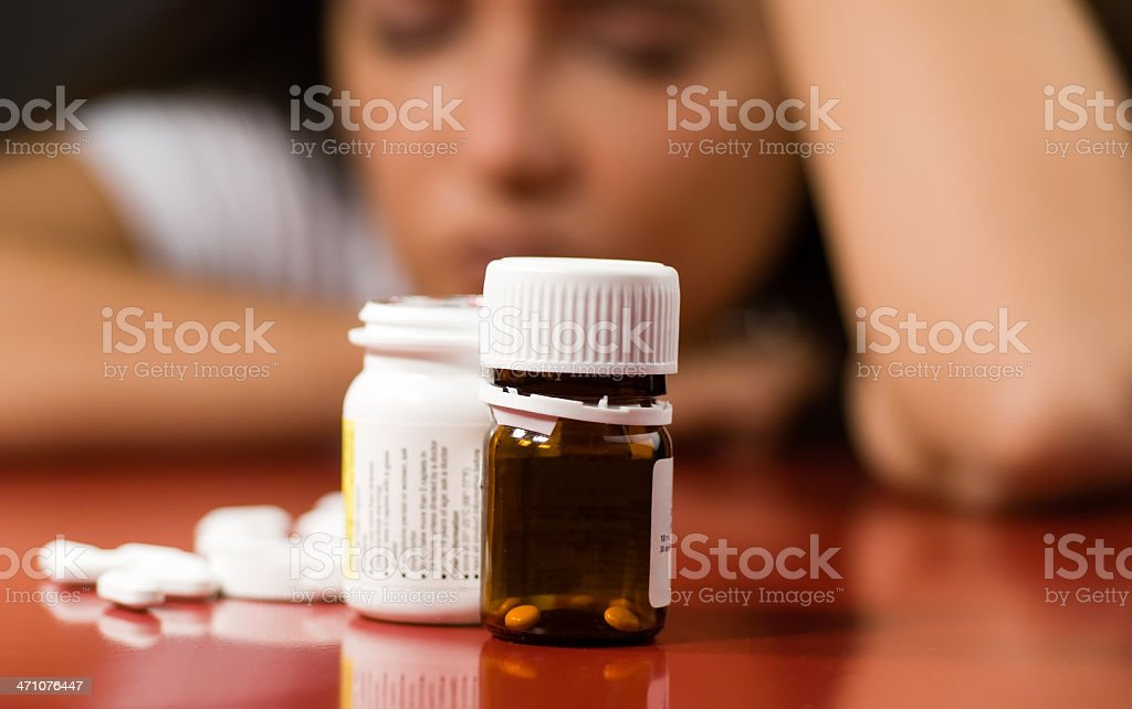 Pill bottles with pills next to them and a woman in back royalty-free stock photo