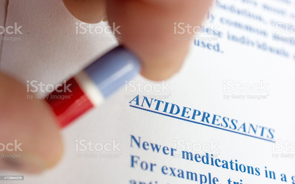 Pill held above a list of adverse antidepressant side effects stock photo