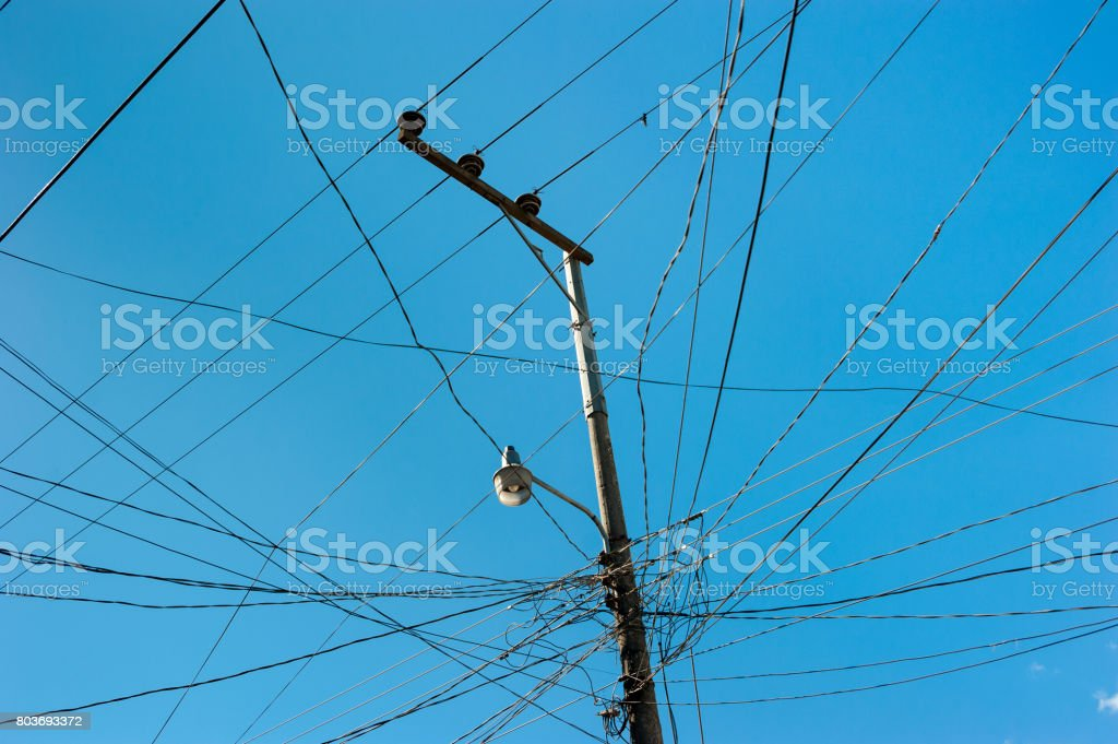 Pillar with lot of wires and a street lamp stock photo