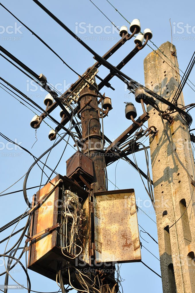 Pillars with old rusty box and crossing cables stock photo