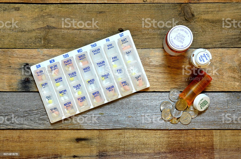 Pillbox with medicine bottle with coins spill out. stock photo