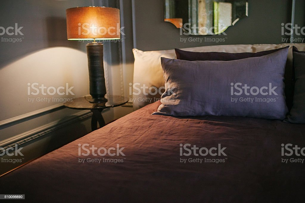 Pillow, bed corner and turned-on lamp at the bedroom stock photo