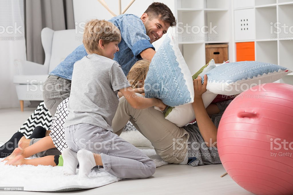 Pillow fight between father and children stock photo