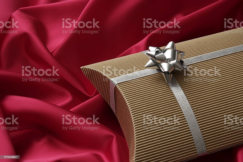 Pillow shape gift box with silver ribbon on red satin royalty-free stock photo