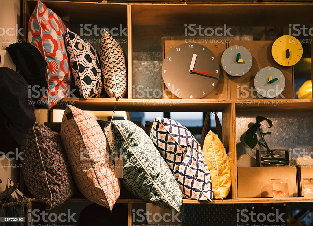 Pillows and handmade clocks in an elegant shop stock photo