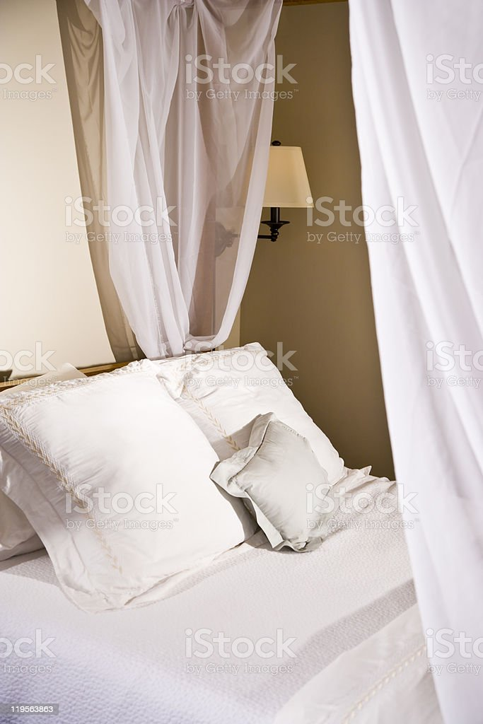 Pillows on a white canopy bed royalty-free stock photo