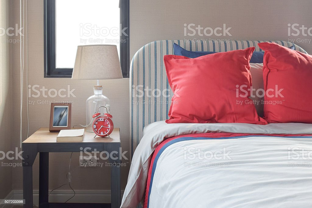 pillows on the cozy bed with striped headboard stock photo