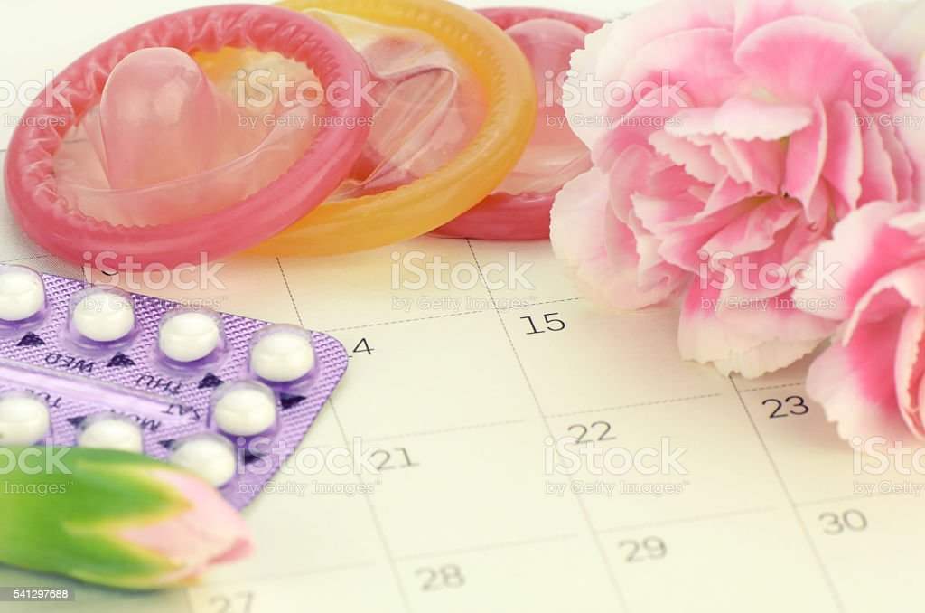 Pills and condom on carlendar background with soft light stock photo