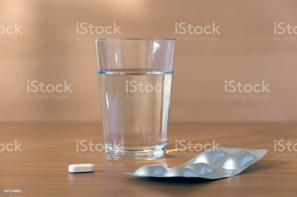 Pills and glass of water stock photo