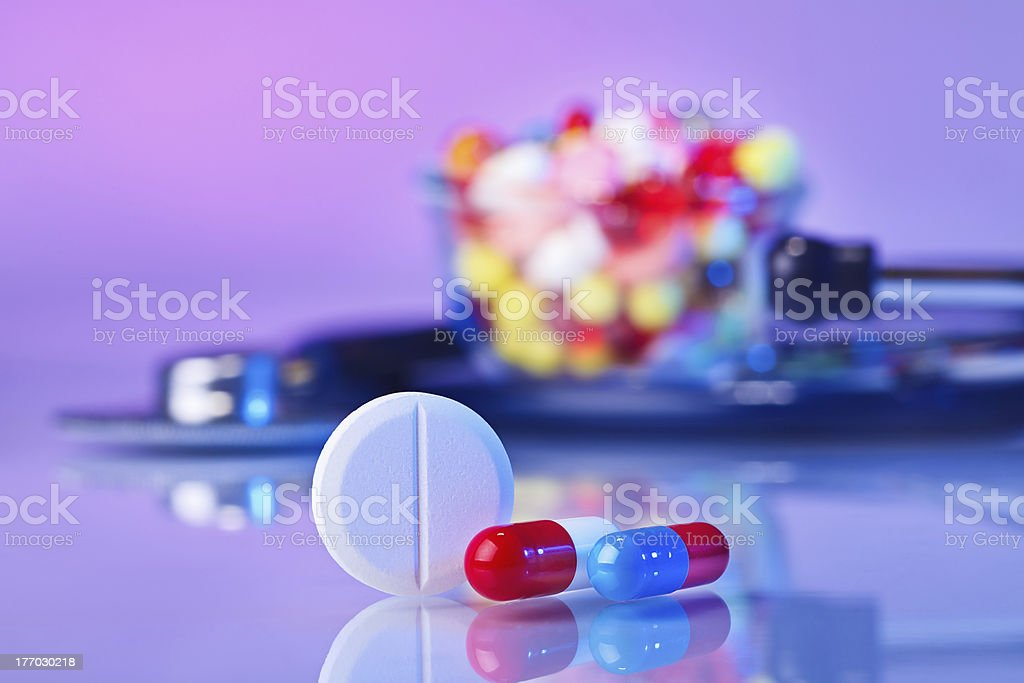 Pills and tablets macro still life on violet, medical concept royalty-free stock photo
