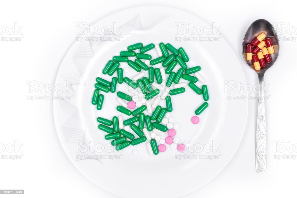 pills are on plate next to spoon with dose stock photo