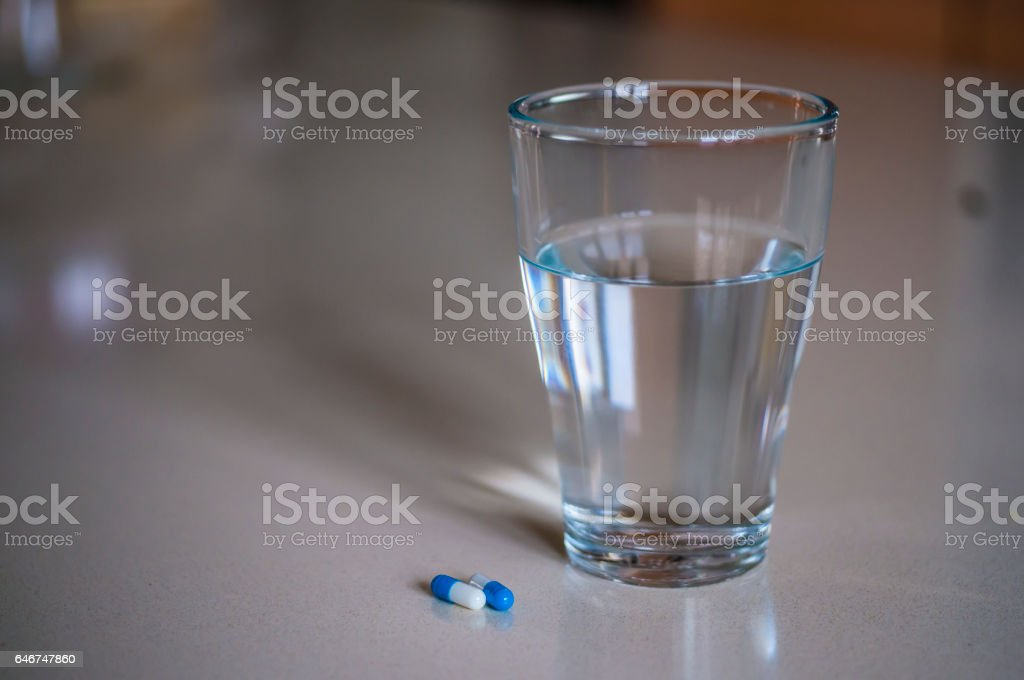 Pills capsules medicine and glass of water stock photo
