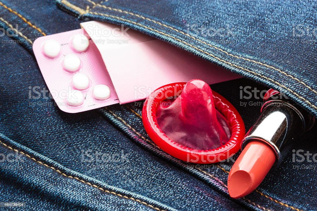 Pills condom and lipstick in denim pocket. stock photo
