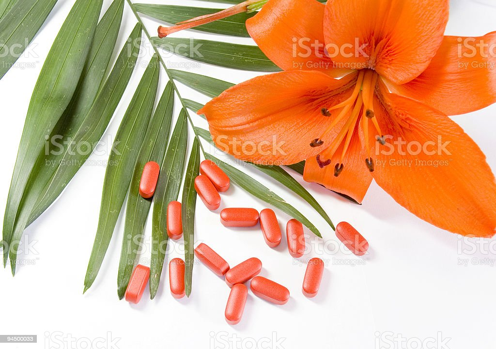pills, flower and the green leaf on a white background royalty-free stock photo