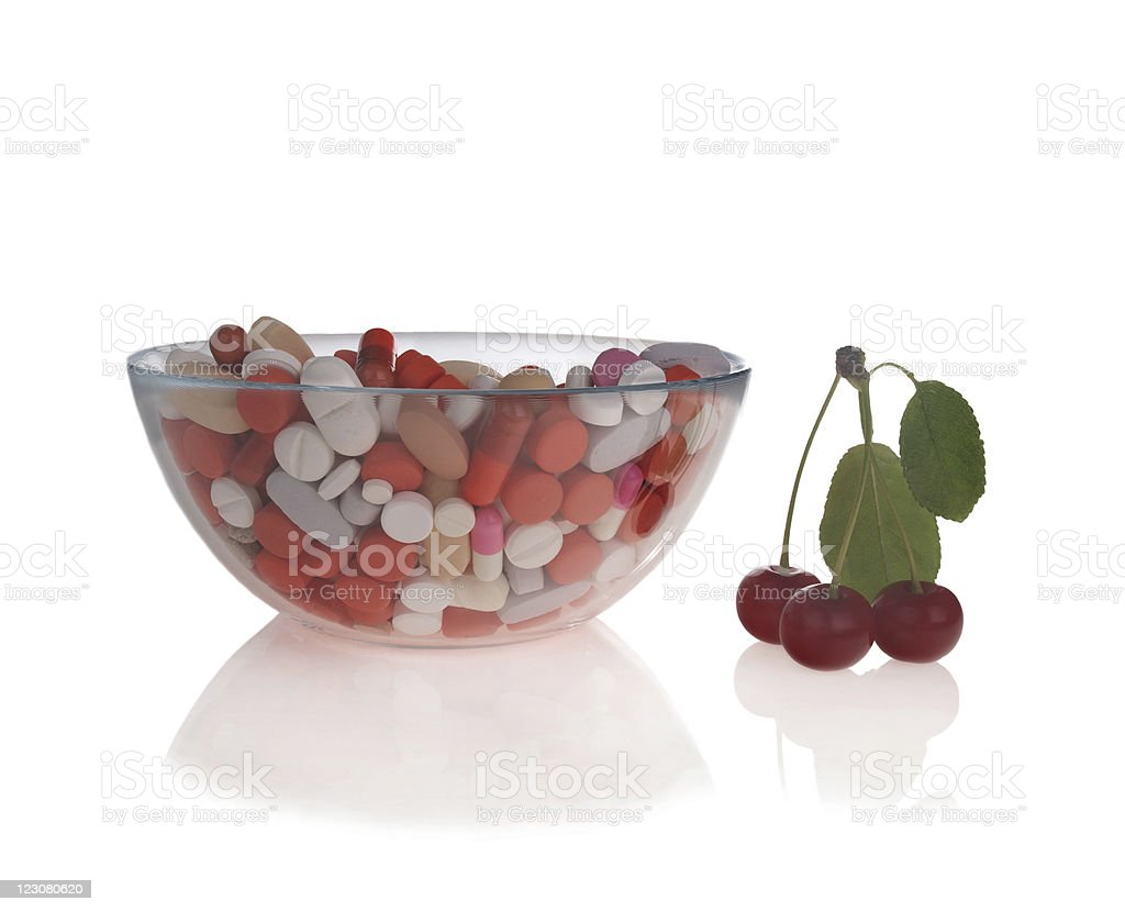 Pills  in glass bowl and sour cherries royalty-free stock photo