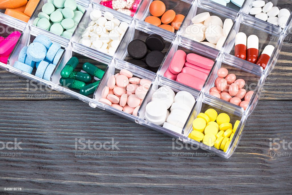 Pills in plastic container on gray tabletop stock photo