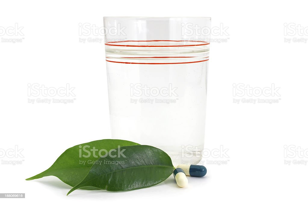 Pills Medicine Capsules and glass with green leaves Bio royalty-free stock photo