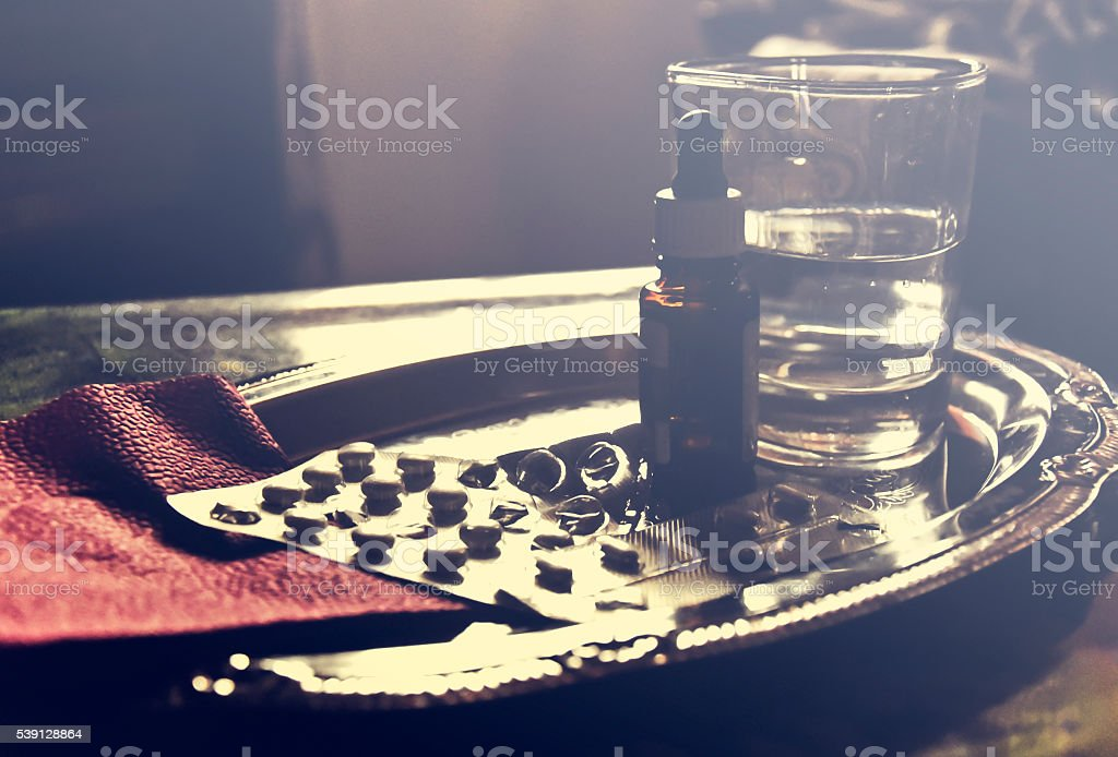 Pills, nasal drops and a glass of water stock photo