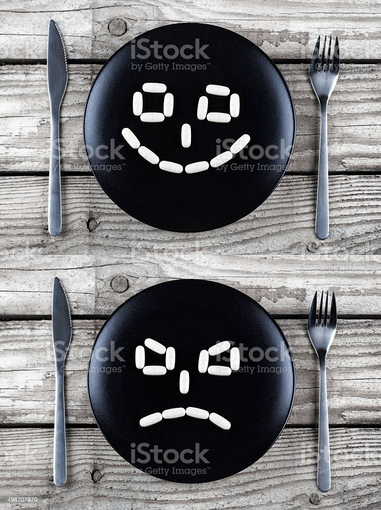 Pills on a black plate - forming faces stock photo