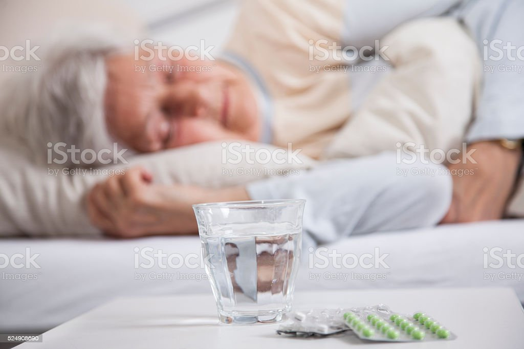 Pills on a night table and senior woman sleeping stock photo