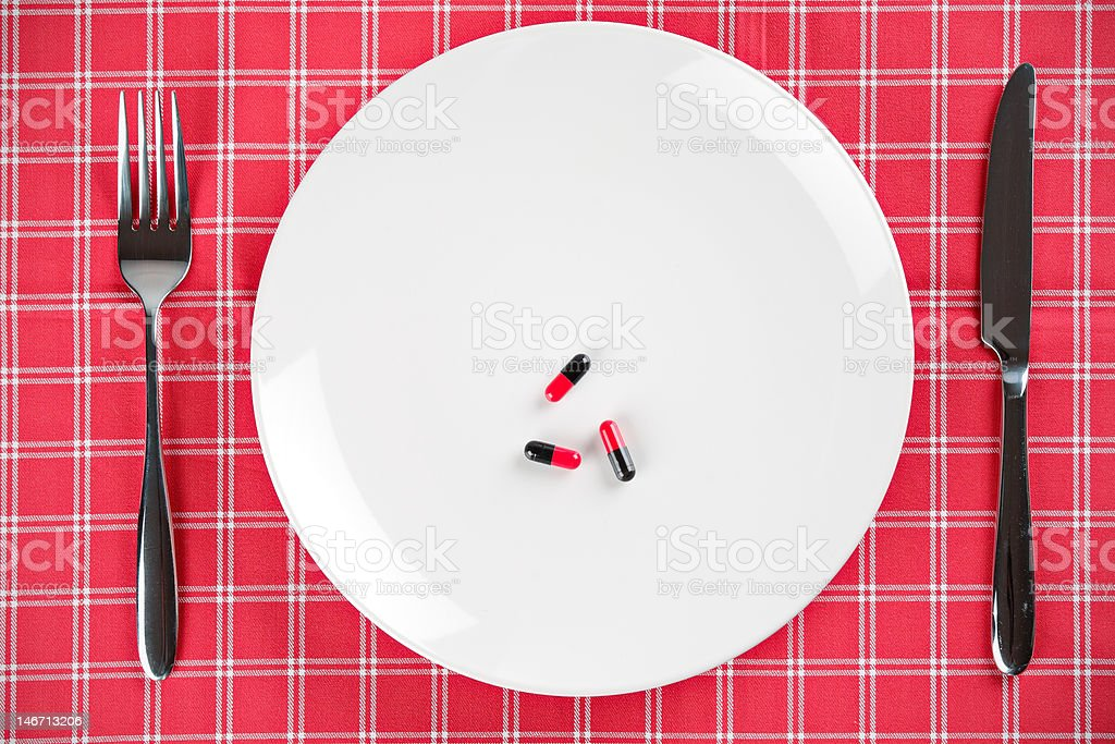 Pills on a white plate with fork and knife royalty-free stock photo