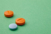 Pills over a green background. Medicament treatment. Health care