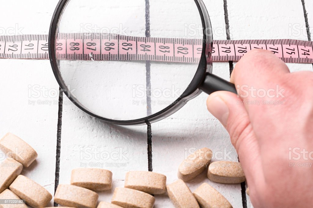 Pills, pink measuring tape and hand holding a magnifying glass stock photo