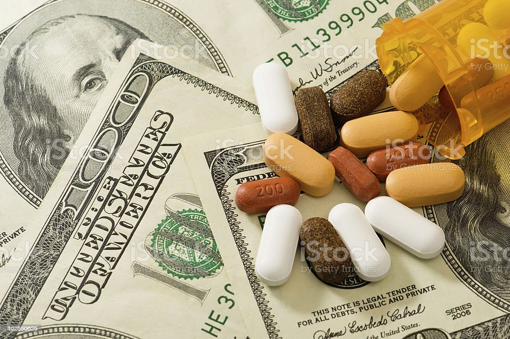 Pills spilled over American bank notes royalty-free stock photo
