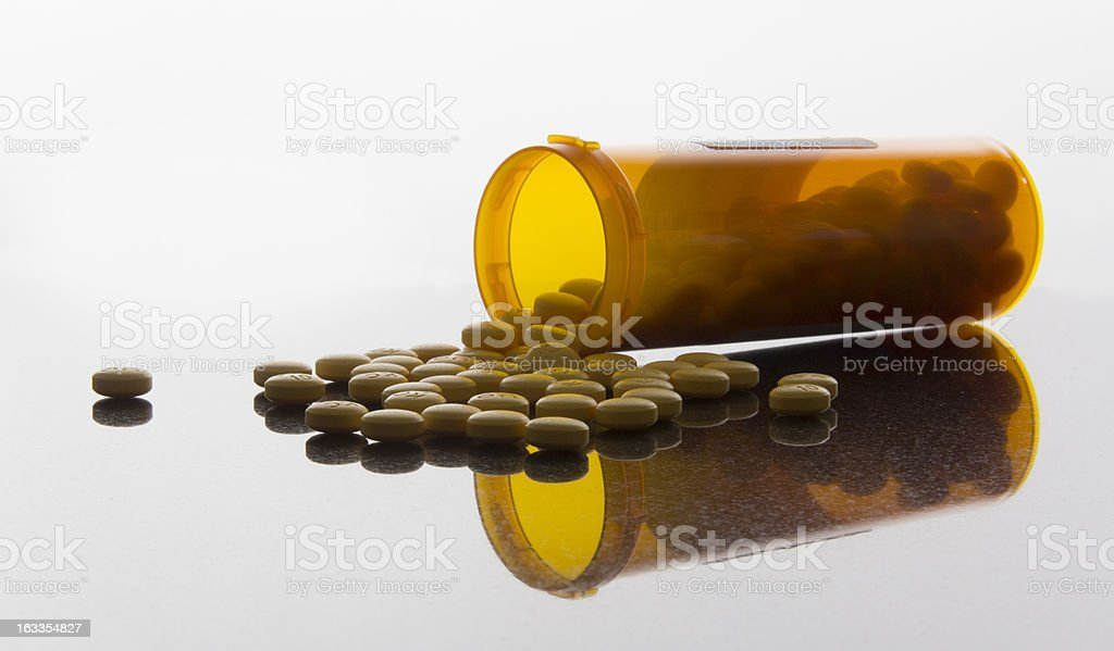 Pills spilling onto a reflective surface royalty-free stock photo