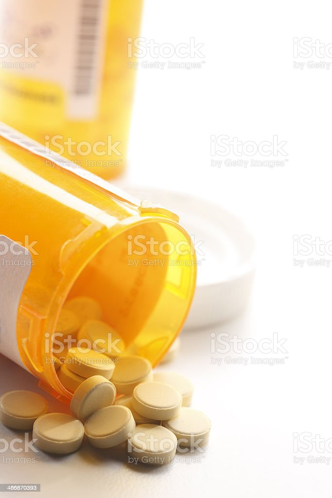 Pills spilling out of a prescription medication bottle royalty-free stock photo