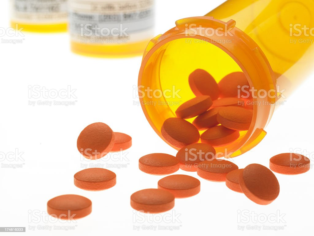 Pills spilling out of bottle on bright white background royalty-free stock photo
