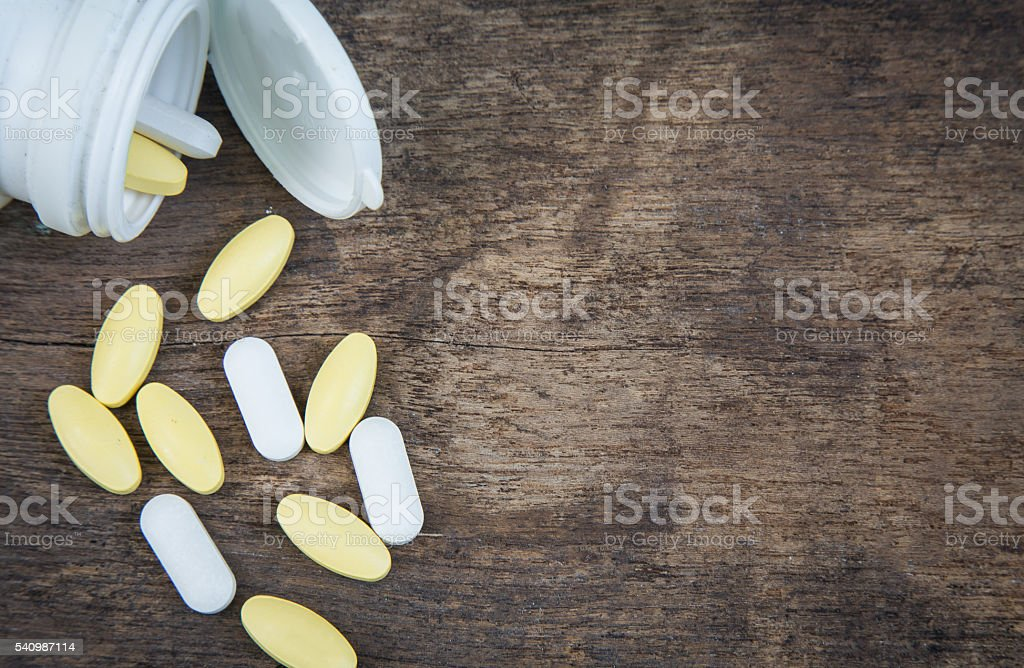 Pills spilling out of pill bottle on wooden background stock photo