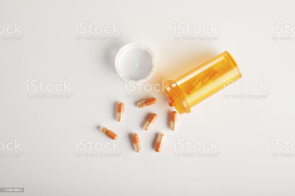 pills spilling out of prescription bottle stock photo