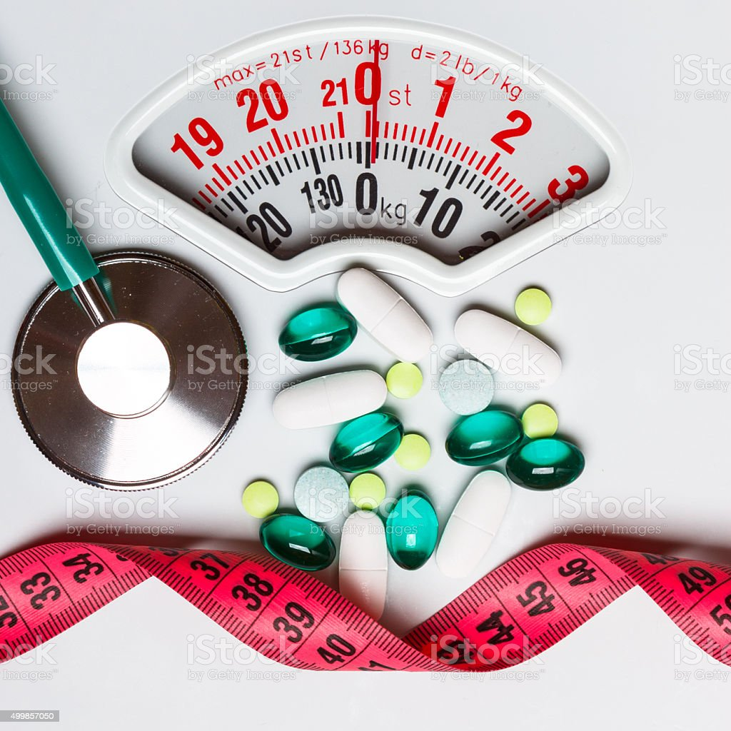 Pills stethoscope measuring tape on scales. Health care stock photo