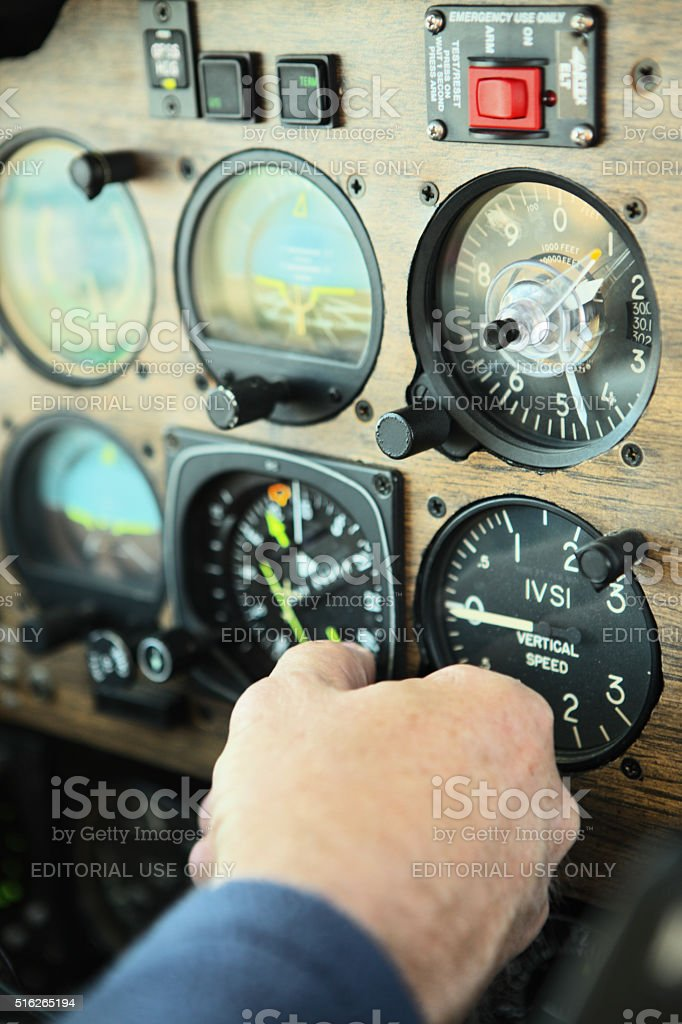 Pilot Adusts Airplane Cockpit Dashboard stock photo
