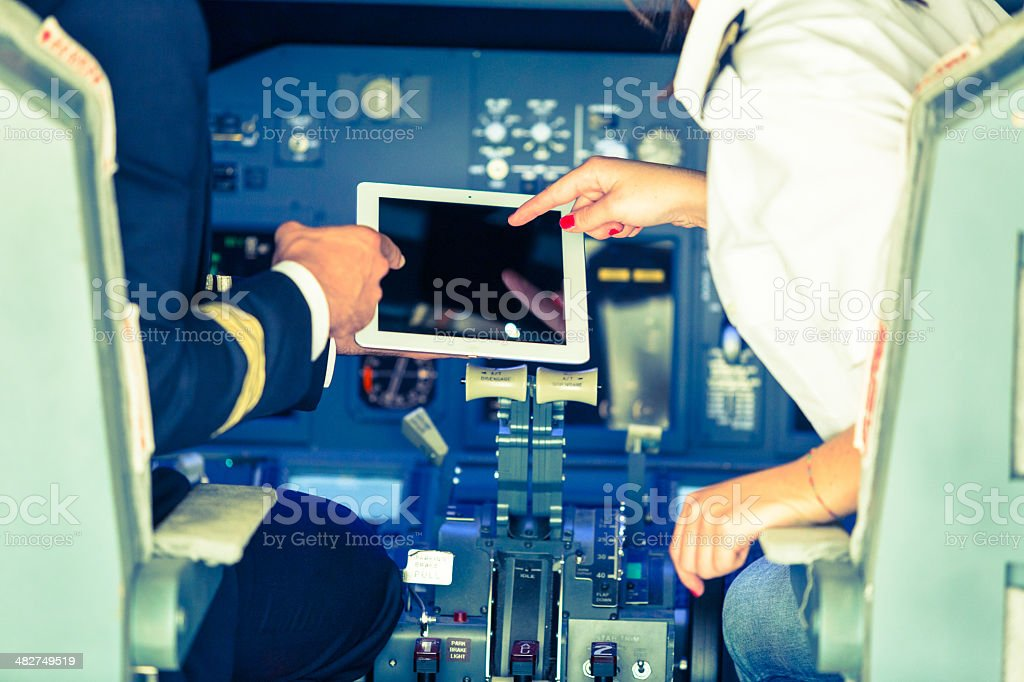 Pilot and Copilot Checking Flight Information on Digital Tablet stock photo