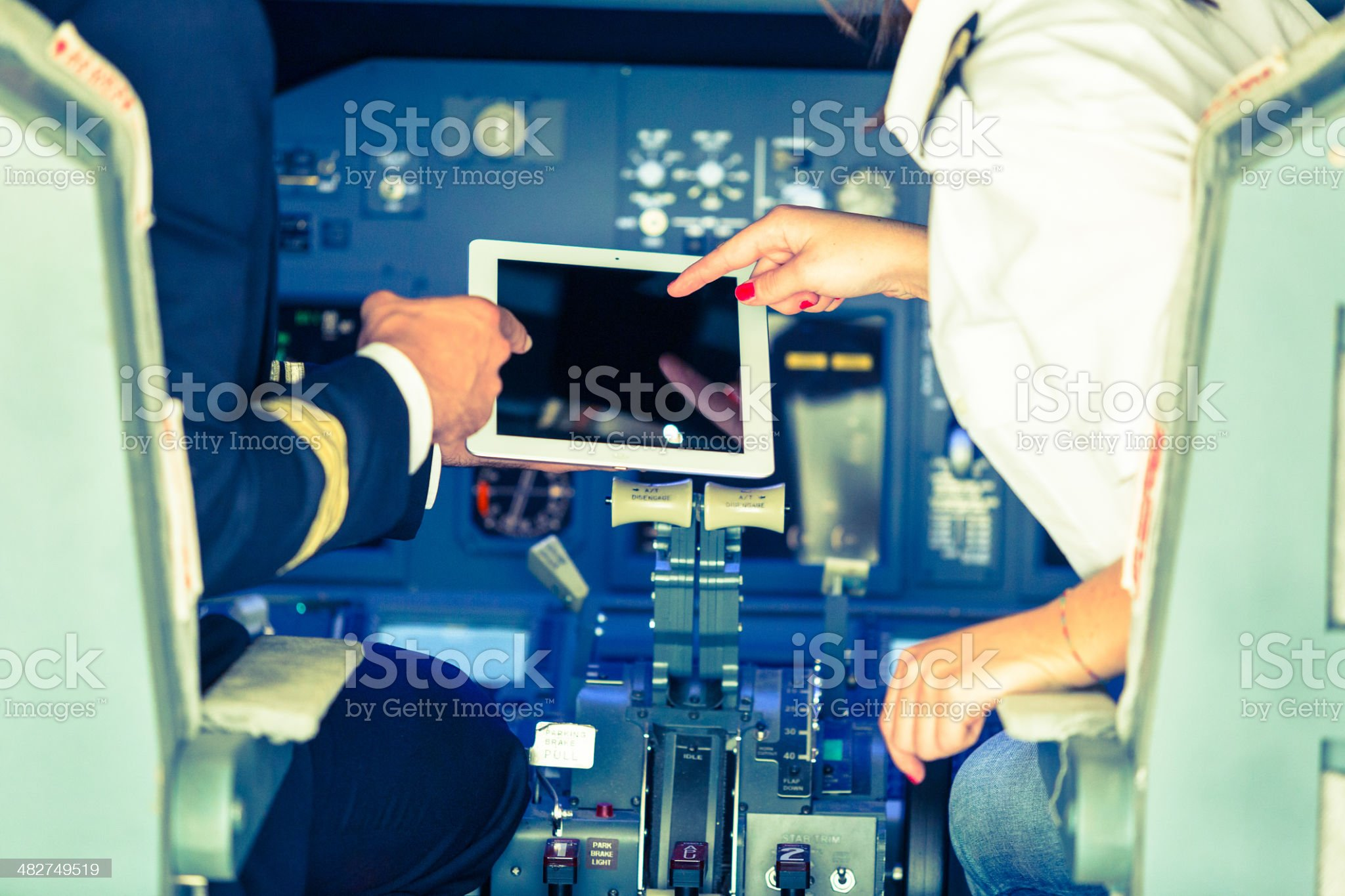 Pilot and Copilot Checking Flight Information on Digital Tablet royalty-free stock photo