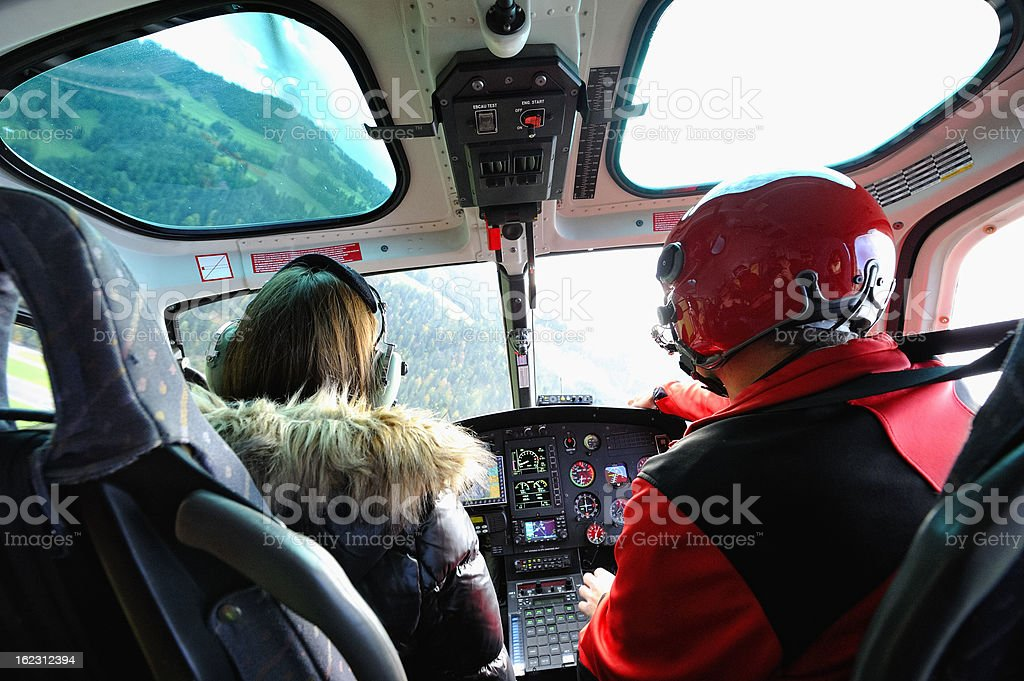 Pilot and Female Passenger in Cockpit of a Modern Helicopter royalty-free stock photo