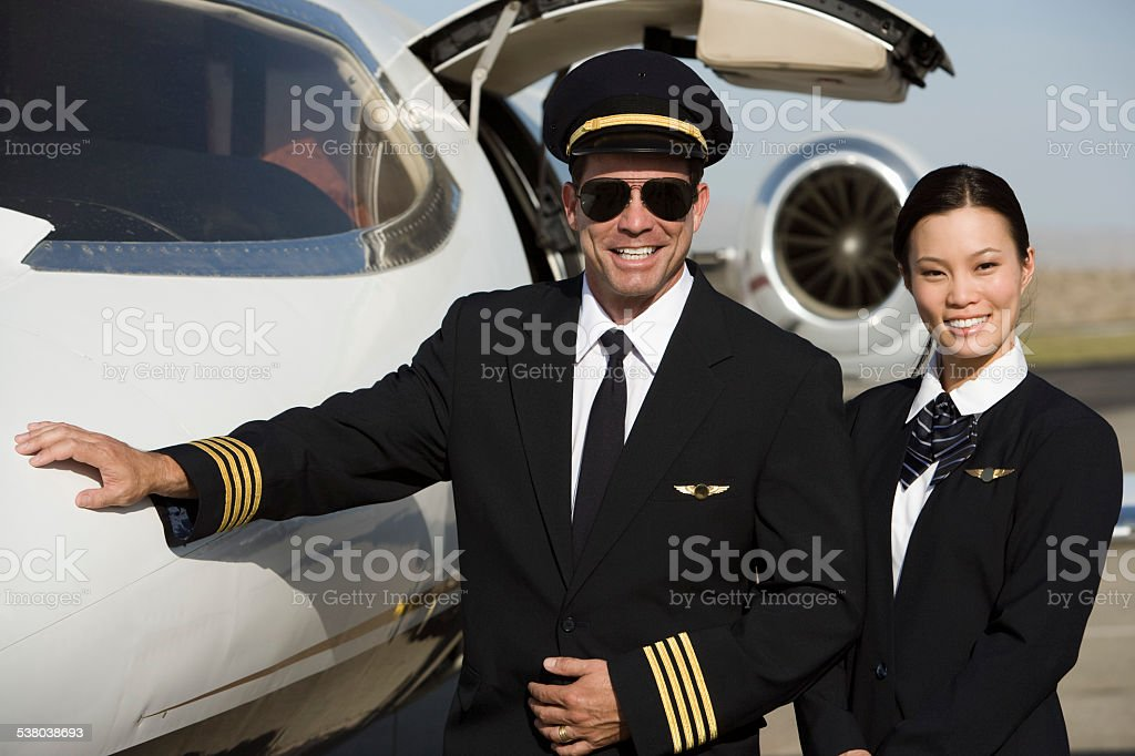 pilot and flight attendant in front of  airplane. stock photo