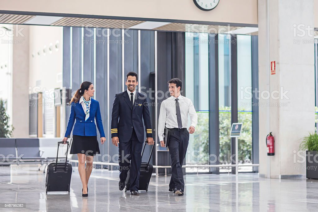 Pilot and flight attendants walking at the airport stock photo