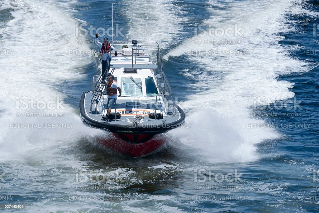 Pilot boat assisting large cruise ship with navigation stock photo