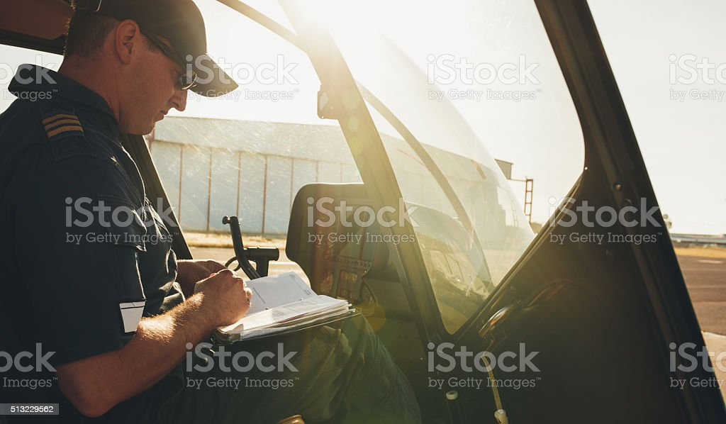 Pilot checking the flight manual before a take off stock photo