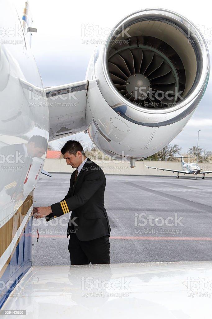 Pilot closing baggage door of the small jet stock photo