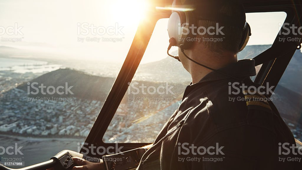 Pilot flying a helicopter and looking outside the window stock photo