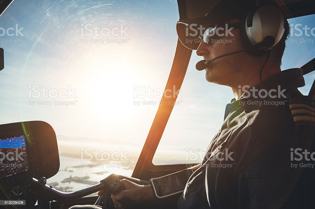 Pilot flying a helicopter on a sunny day stock photo
