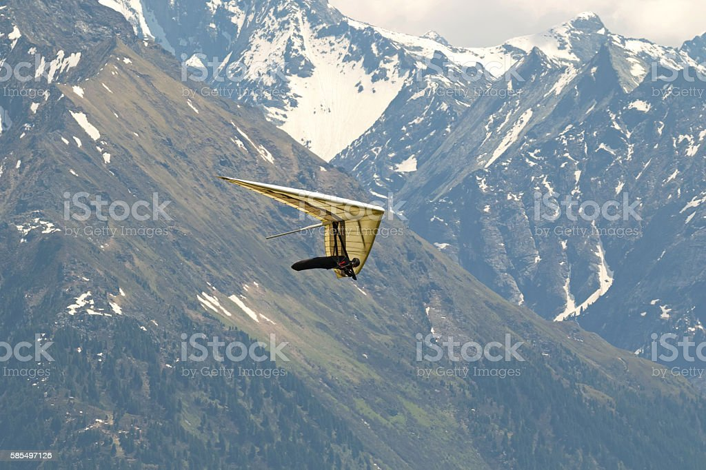 Pilot flying foot launched Hang glider with Zillertal Alps mountain stock photo