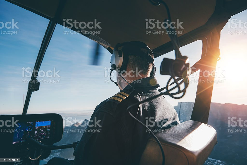 Pilot flying helicopter on a sunny day stock photo
